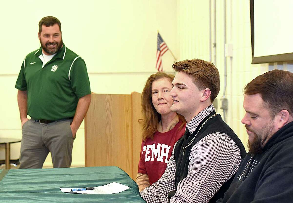 Norwalk High football player James Makszin, second from right, signed his National Letter of Intent to play football at Division 1 Temple University during a brief signing ceremony at the school on Wednesday. Makszin is flanked by his mother, left, and uncle as Bears football coach Sean Ireland oversees the signing.