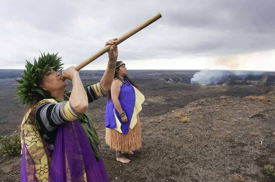 Ehulani Stephany, a high priestess of hula kahiko, Hawaii's indigenous dance, song, and ritual, plays a bamboo ohepu while her student, Uilani Pihana, performs a sacred hula near the lip of Kilauea's 2-mile-wide caldera. Photo: Jeff Greenwald, Special To The Chronicle