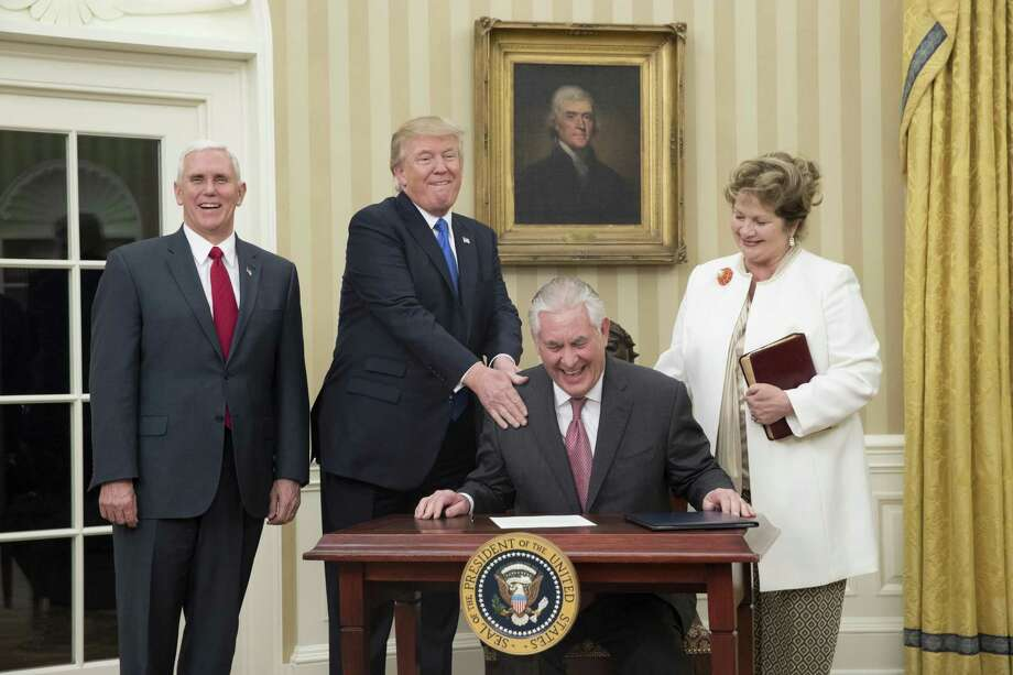 WASHINGTON, DC - FEBRUARY 1:  (AFP OUT) U.S. President Donald Trump (2nd L) reacts after  Rex Tillerson (seated), accompanied by wife Renda St. Clair, signed an appointment affidavit after being sworn in as the 69th secretary of state by Vice President Mike Pence (L) in the Oval Office of the White House on February 1, 2017 in Washington, DC. Tillerson was confirmed by the Senate earlier in the day in a 56-43 vote.  (Photo by Michael Reynolds-Pool/Getty Images) Photo: Pool, Pool / Getty Images / 2017 Getty Images