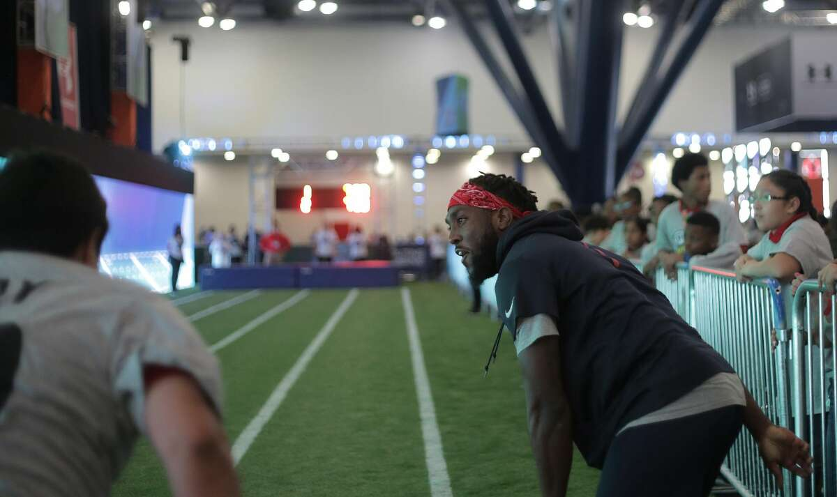 Akeem Hunt helps out area school kids participate in a timed forty-yard dash during the NFL Experience as part of the NFL Play 60 Kids' Day on Wednesday, Feb. 1, 2017, in Houston. ( Elizabeth Conley / Houston Chronicle )