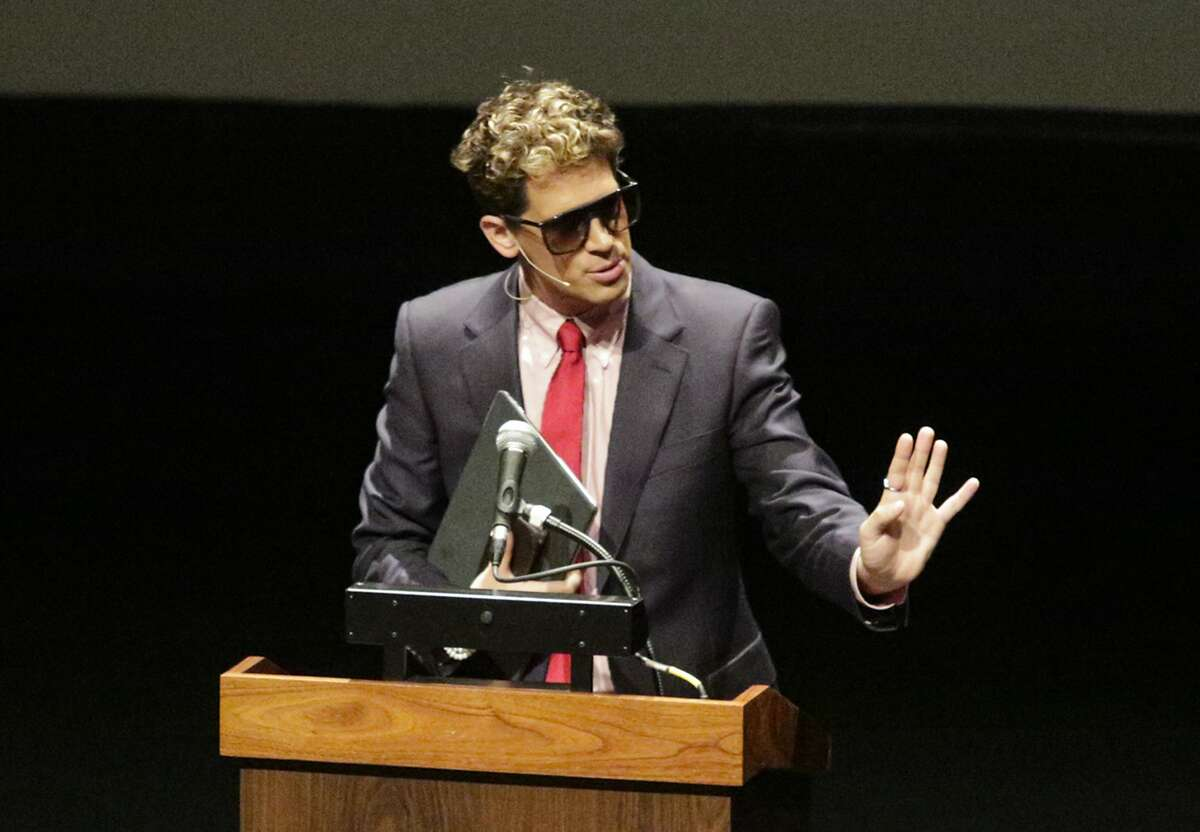 """Milo Yiannopoulos, the polarizing Breitbart News editor, speaks at California Polytechnic State University as part of his """"The Dangerous Faggot Tour"""" of college campuses, Tuesday, Jan. 31, 2017, in San Luis Obispo, Calif. His speech was met with dozens of angry protesters outside a campus theater. (David Middlecamp/The Tribune (of San Luis Obispo) via AP)"""