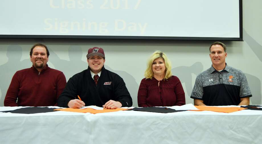 EHS senior Tate Rujawitz, seated second to left, will play football at SIUC. His parents, Tony, left, and Lori, second to right, join him for Signing Day along with EHS coach Matt Martin.
