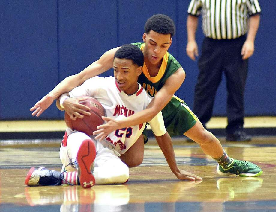 Brien McMahon's Eric Day, left, finds himself tied up by Trinity Catholic's Stephon McGill in the first half of Wednesday's game in Norwalk. Photo: John Nash / Hearst Connecticut Media / Norwalk Hour