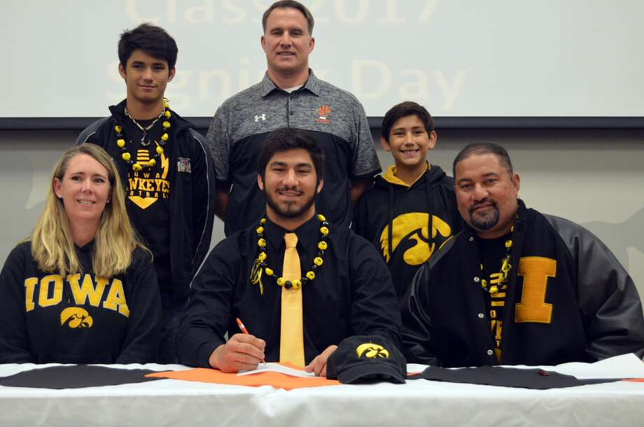 EHS senior AJ Epenesa, seated center, will play football at Iowa. Seated next to him are his parents, Stephanie and Eppy. Standing are his brothers Eric, left, and Iose, right, with EHS coach Matt Martin.