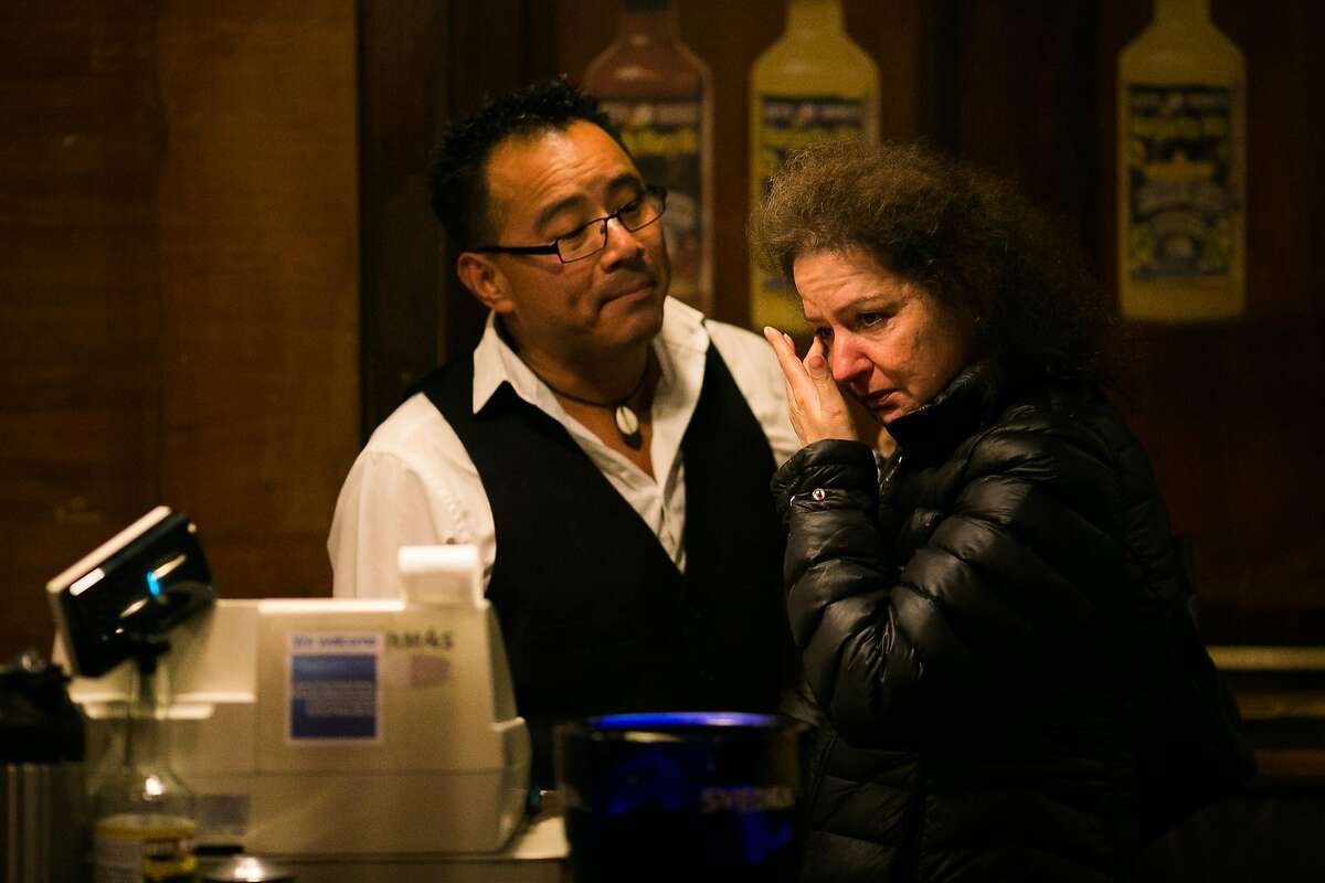 Lefty O'Doul's Restaurant & Cocktail Lounge employees Julio Ramirez, left, comforts Stacy Selder as they held their final party at the 333 Geary Street location in San Francisco, Calif., Monday, February 01, 2017. Nick Bovis, proprietor of Lefty O'Doul's, plans to move the restaurant and the memorabilia to a new location by late fall.