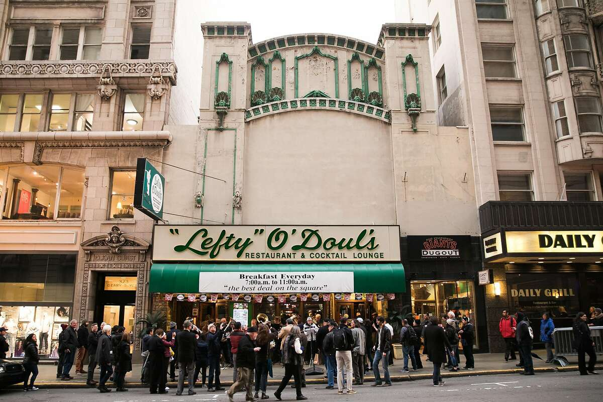 People gather around Lefty O'Doul's Restaurant & Cocktail Lounge to see The Deutscher Musikverein of San Francisco play at the 333 Geary Street location in San Francisco, Calif., Monday, February 01, 2017. Nick Bovis, proprietor of Lefty O'Doul's, plans to move the restaurant and the memorabilia to a new location by late fall.