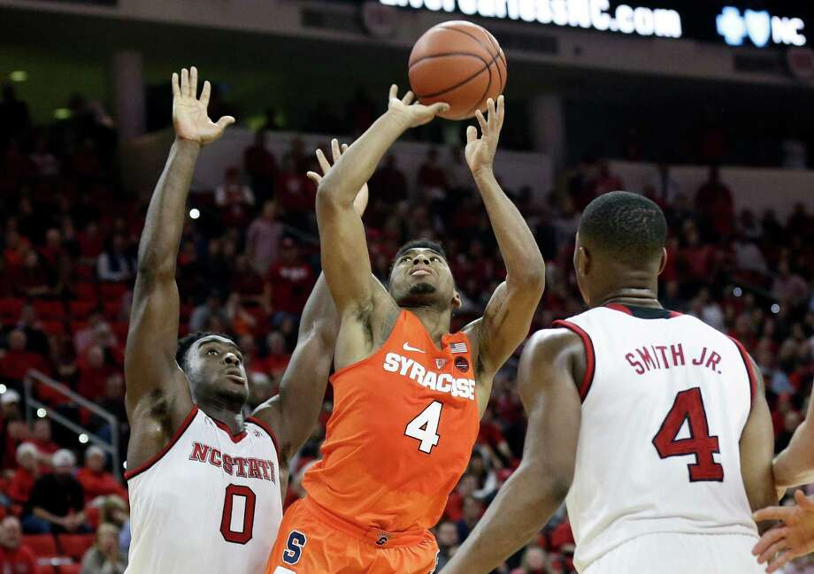 Syracuse's John Gillon (4) shoots against North Carolina State's Abdul-Malik Abu (0) and Dennis Smith Jr. (4) during the second half of an NCAA college basketball game in Raleigh, N.C., Wednesday, Feb. 1, 2017. Syracuse won 100-93 in overtime. (AP Photo/Gerry Broome) ORG XMIT: NCGB107 Photo: Gerry Broome / Copyright 2017 The Associated Press. All rights reserved.