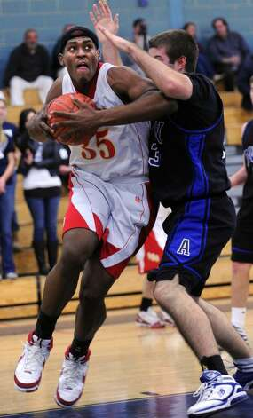 Stratford's Brandon Sherrod knocks into Avon's Andrew McGee on his way to the net during the Class L quarterfinal tournament game Friday Mar. 12, 2010 at Kennedy High School in Waterbury. Photo: Autumn Driscoll, ST / Connecticut Post