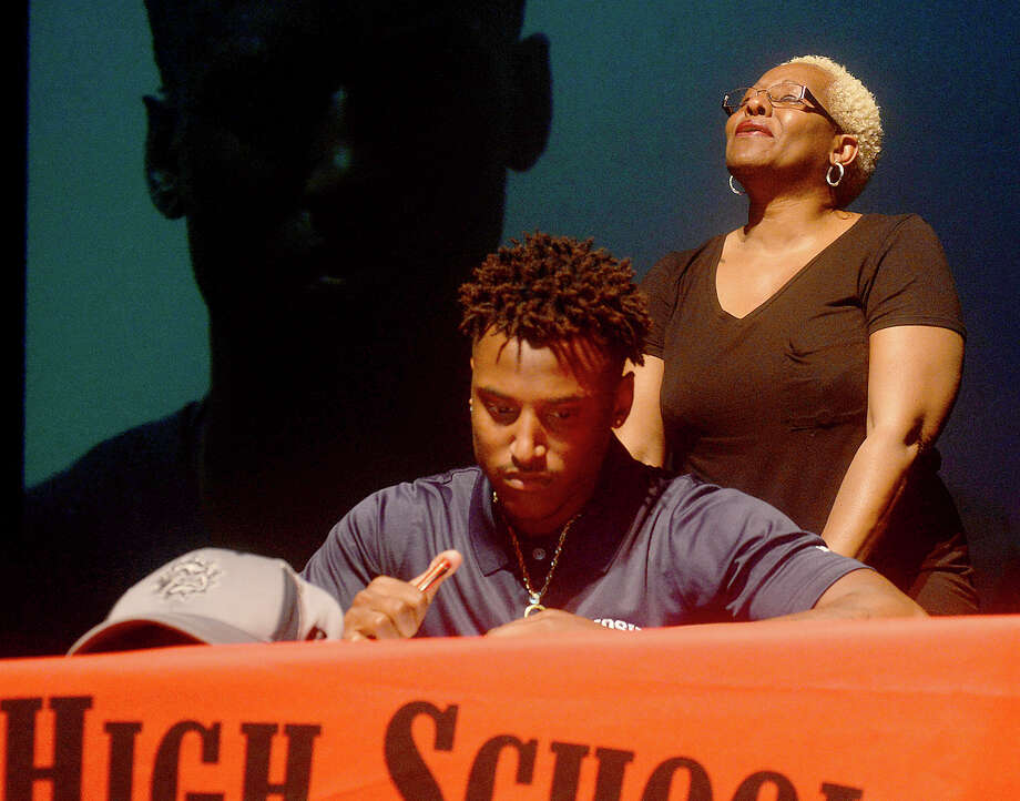 Port Arthur - Memorial's is flanked by family as he signs and dons his new college ball cap during the Titans' spirited National Signing Day event Wednesday in the school auditorium. Photo taken Wednesday, February 1, 2017 Kim Brent/The Enterprise Photo: Kim Brent / Beaumont Enterprise