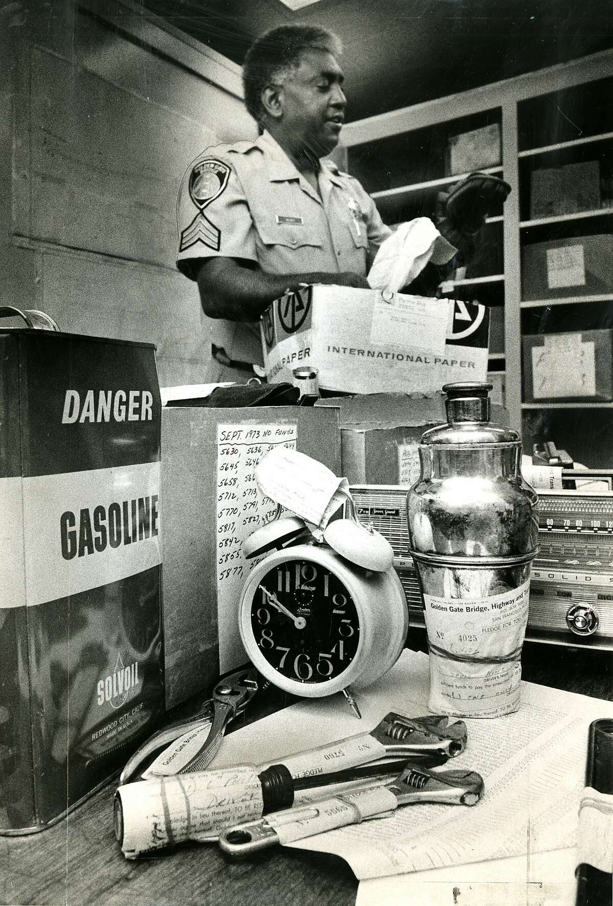 June 9, 1975: Charles Volivet examines items that were left, as security, by motorists who didn't have toll money. The items in the photo include a horse hair brush, alarm clock, transistor radios, and a pair of wrenches. The items were later auctioned off. Toll fees in the 1970's: December 1, 1969: 25-trip discount toll ticket book available for $10 (40 cents/trip) December 25, 1971 Replaced discount toll ticket books with 20-trip convenience ticket book for $10 (50 cents/trip) March 1, 1974 75 cents southbound toll, free northbound, and 20-trip convenience ticket book for $15 (75 cents/trip)
