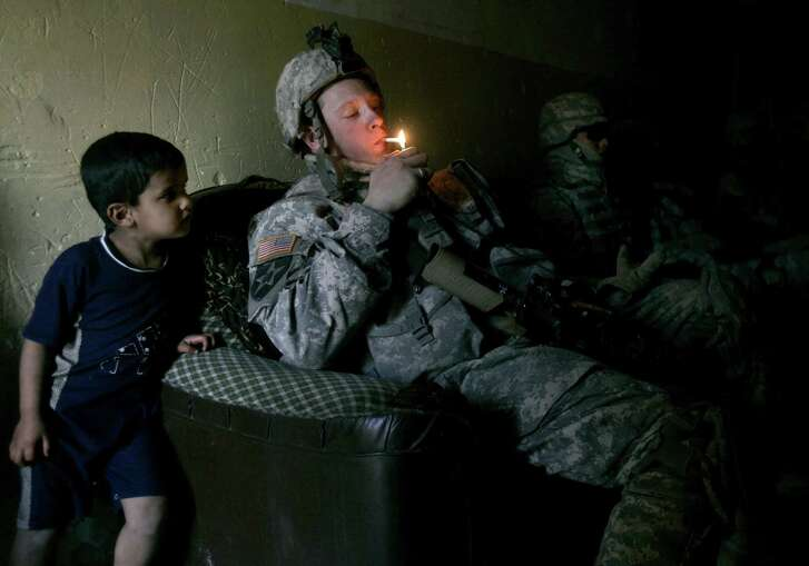 A    soldier  lights up a cigarette as his unit takes a rest after a foot patrol in Baghdad's Shiite enclave of Sadr City, Iraq, in 2007. Legislation to increase the smoking age should include our young troops — to give them a chance at a healthy life.
