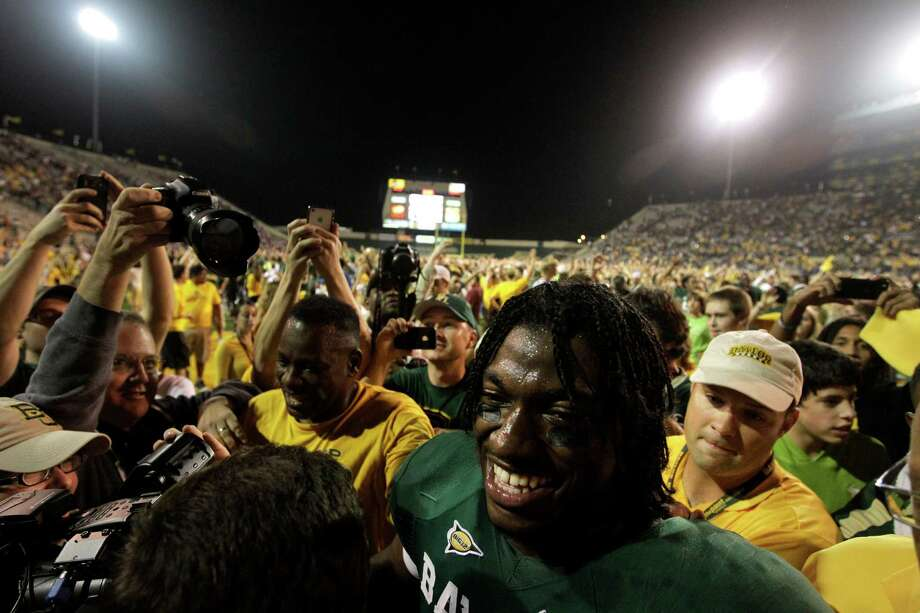 Baylor quarterback Robert Griffin III (10) makes his way by fans who stormed the field following an NCAA college football game against Oklahoma Saturday, Nov. 19, 2011, in Waco, Texas. Baylor won 45-38. Photo: Tony Gutierrez, AP / 2011 AP