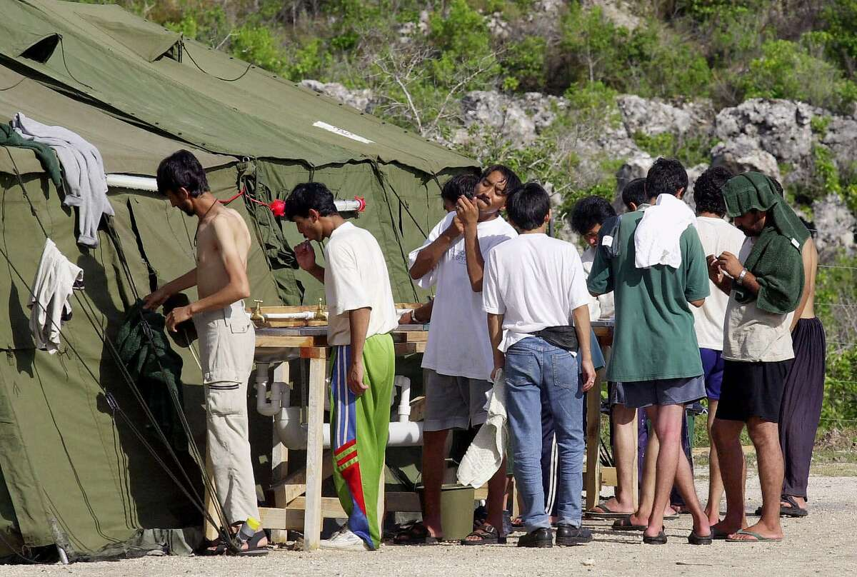 FILE - In this Sept. 21, 2001, file photo, men shave, brush their teeth and prepare for the day at a refugee camp on the Island of Nauru. Australia's Prime Minister Malcolm Turnbull insisted Thursday, Feb. 2, 2017, that a deal struck with the Obama administration that would allow mostly Muslim refugees rejected by Australia to be resettled in the United States was still on, despite President Donald Trump dubbing the agreement