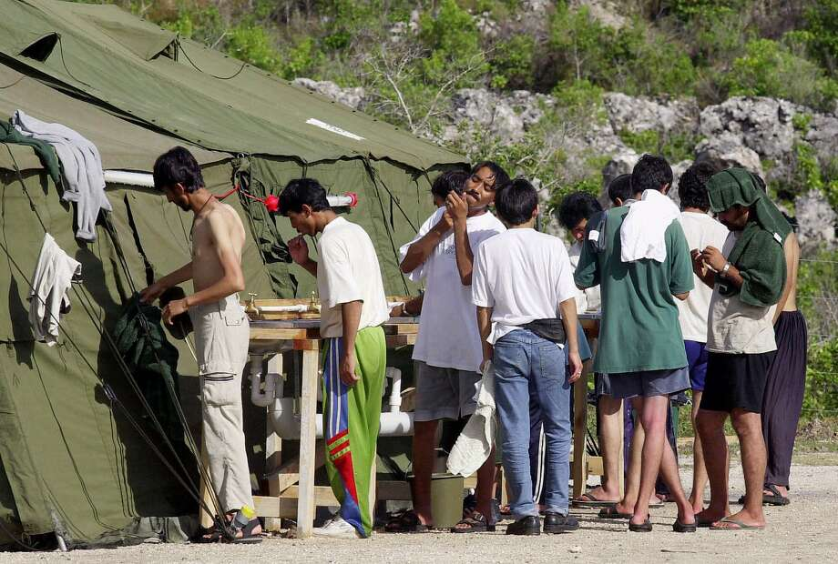 Men prepare for the day in 2001 at a refugee camp on the Island of Nauru. Photo: Rick Rycroft, Associated Press