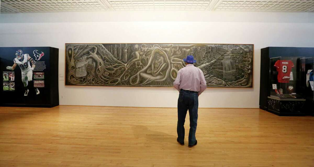 """Ronald """"Buck"""" Goodbeer, 70, of Houston, takes a moment to look at John T. Biggers' """"Web of Life"""" mural at Texas Southern University's University Museum Thursday, Feb. 2, 2017, in Houston. The famous mural is placed between the Hometown Heroes, left, and Dynasties sections of the Gridiron Glory: The Best of the Pro Football Hall of Fame exhibition."""