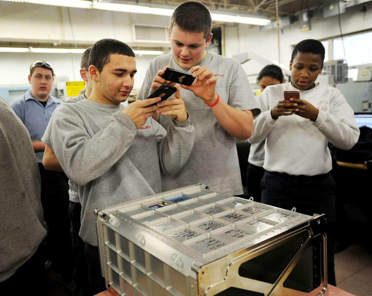 From left; students Danny Luperella, 16, of Milford, Nate Moreland, 16, of Seymour, and Cheyenne Saunders, 16, of West Haven, snap photos of the aluminum stowage locker that they helped manufacture for the International Space Station at Platt Tech in Milford, Conn. on Thursday, February 2, 2017. NASA's HUNCH program works with students at one hundred schools in twenty-six states to manufacture equipment for the space program.