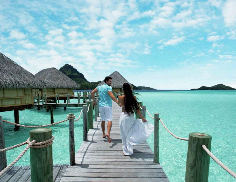 The thatched-roof bungalows over crystal blue waters in Bora Bora help make this a honeymooners' delight. Photo: Courtesy Grégoire Le Bacon /Tahiti Tourism