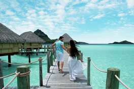 The thatched-roof bungalows over crystal blue waters in Bora Bora help make this a honeymooners' delight.