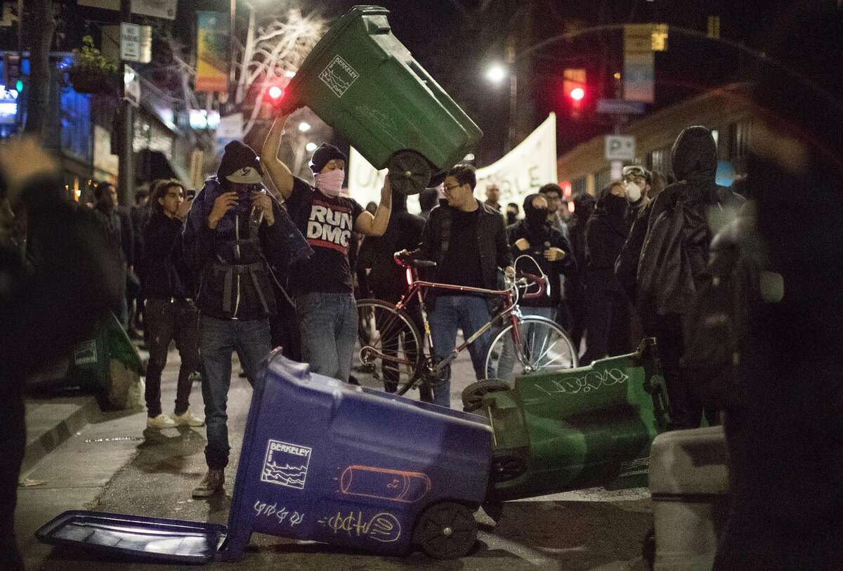 A protesters dumps a trash can in the middle of Telegraph Ave. on Wednesday, Feb. 1, 2017 in Berkeley, Calif.