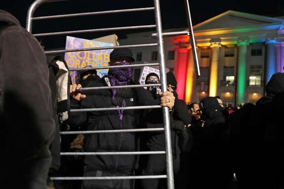 A member of the Black Bloc holds a section of security fencing as demonstrations forced the cancellation of a talk by right-wing provocateur Milo Yiannopoulos in Berkeley, Calif., on Wednesday, February 1, 2017.