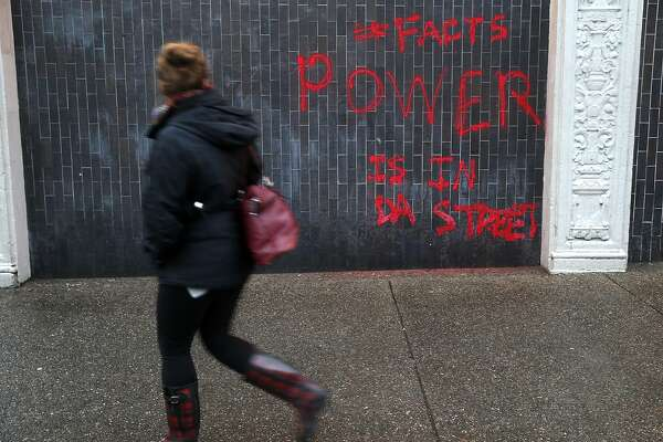 A woman walks past graffiti sprayed on the Bank of America branch at Telegraph and Durant avenues in Berkeley, Calif. on Thursday, Feb. 2, 2017 after Wednesday night's planned protest against an appearance by Breitbart writer Milo Yiannopoulos on campus turned violent.