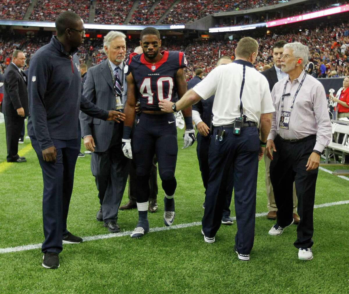 Dr. Arthur Day helps to escort Kurtis Drummond (40) back to the locker room after an injury during the second quarter of an NFL game at NRG Stadium on Sunday, Nov. 1, 2015, in Houston.