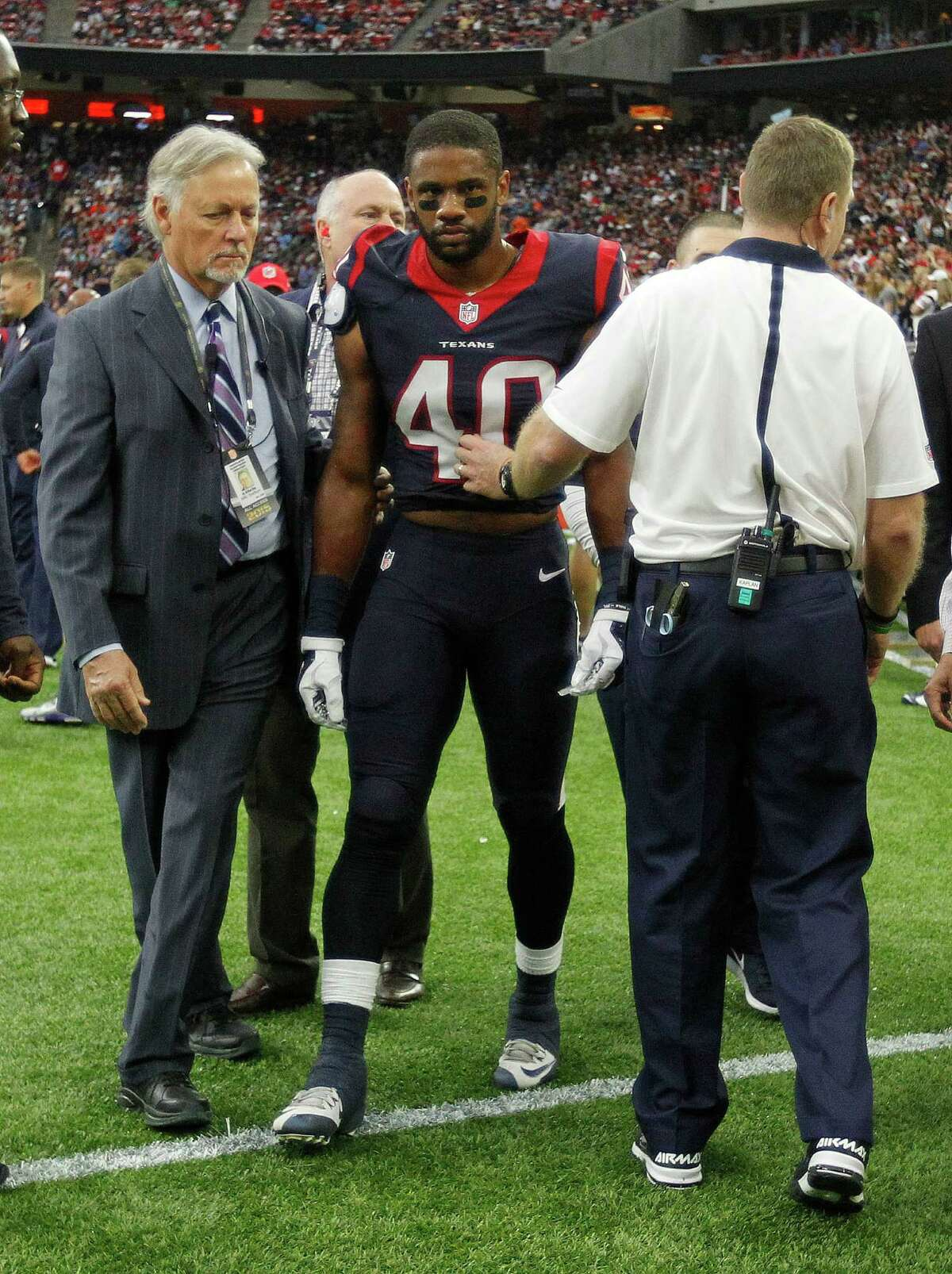Dr. Arthur Day, a professor of neurosurgery at UTHealth, helps to escort Kurtis Drummond (40) back to the locker room after an injury during the second quarter of an NFL game at NRG Stadium on Sunday, Nov. 1, 2015, in Houston.