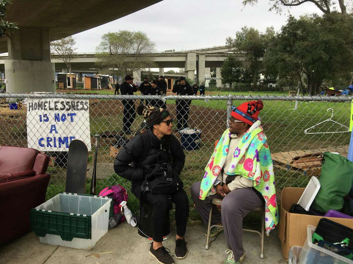 Nancy Mitchell (right) talks with Rae, who only gave her first name, after she was told to leave a park Thursday morning that had been turned into a village for the homeless.