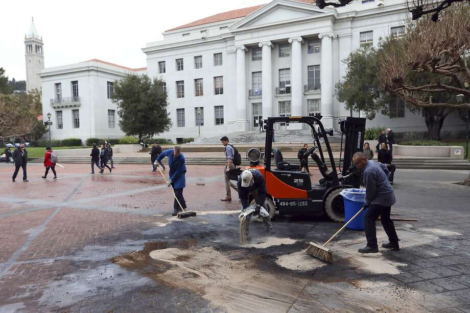 Workers clean up a an area where a mobile light tower stood which was set on fire during protests against a planned speech by right-wing writer Milo Yiannopoulos at the University of California, Berkeley, Feb. 3, 2017. The university announced the cancellation of Yiannopoulos� speech about an hour after the protests began Wednesday night. Photo: JIM WILSON, NYT