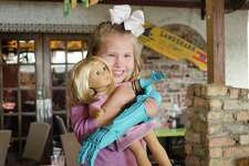 Izzy Miller, 8, received an American Girl doll with a matching prosthetic arm at Cafe Del Rio on Thursday. The doll was a gift from, West Brook principal Dr. Diana Valdez, robotics and computer science West Brook teacher Joy Schwartz, West Brook robotics students and the West Brook Stars drill team. Photo taken Thursday, February 2, 2017 Sara E. Flores/The Enterprise