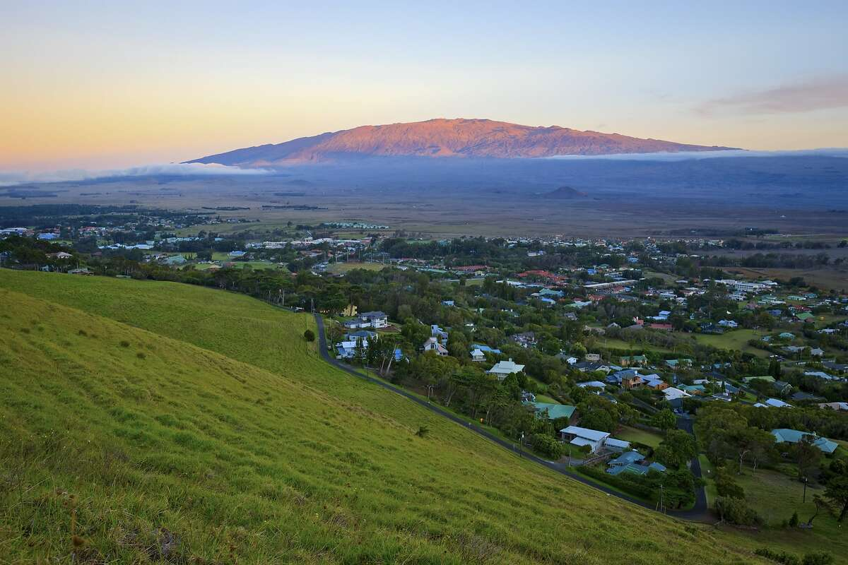 Mauna Kea, the highest mountain in the world as measured from the ocean floor, looms beyond the former ranch town of Waimea, which now includes headquarters for observatories atop the sacred peak.