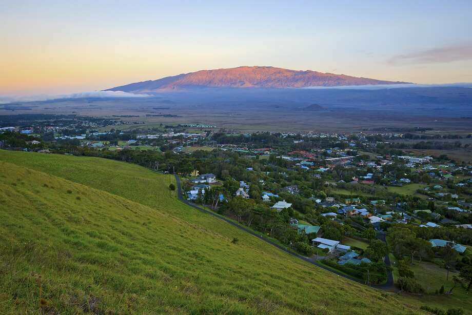 Mauna Kea, the highest mountain in the world as measured from the ocean floor, looms beyond the former ranch town of Waimea, which now includes headquarters for observatories atop the sacred peak. Photo: Ethan Tweedie / IHVB