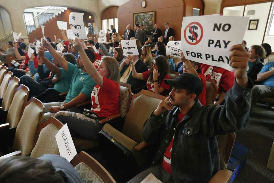 Activists hold up signage as City Council votes on approving an agreement between Hemisfair Park Area Redevelopment Corporation and ZH Downtown Development Company - an affiliate of Zachary Hospitality on Thursday, Feb. 2, 2017. The council heard proponents and opponents of the agreement. The opposing voices and concerns from citizens were about alleged contributions to council members and Mayor Ivy Taylor from Zachary along with opposition from Unite Here! San Antonio whom are arguing against a future hotel to be built on the Hemisfair grounds. (Kin Man Hui/San Antonio Express-News) Photo: Kin Man Hui, Staff / San Antonio Express-News / ©2017 San Antonio Express-News