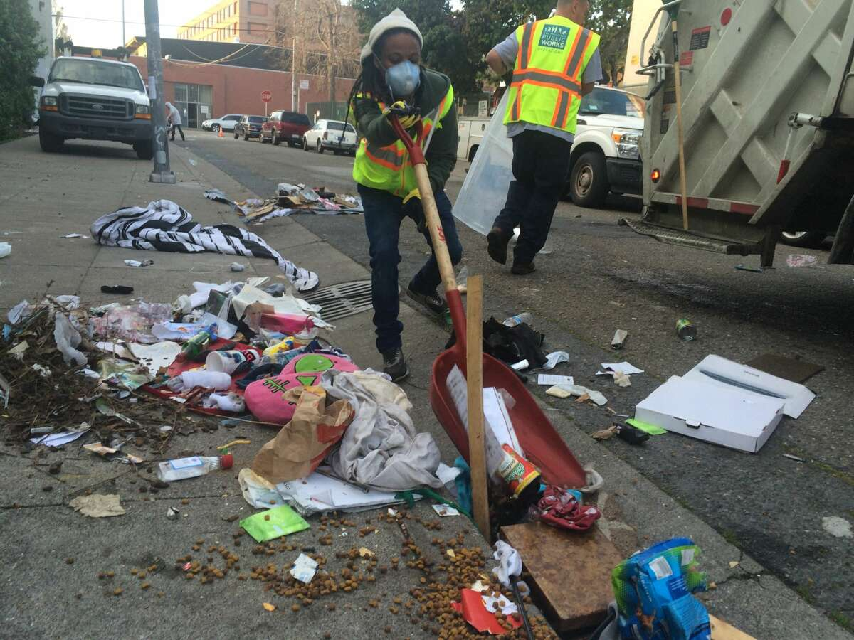 A city Department of Public Works employee cleaner cleans up a mess on a Tenderloin street. Human excrement is often part of the mess.