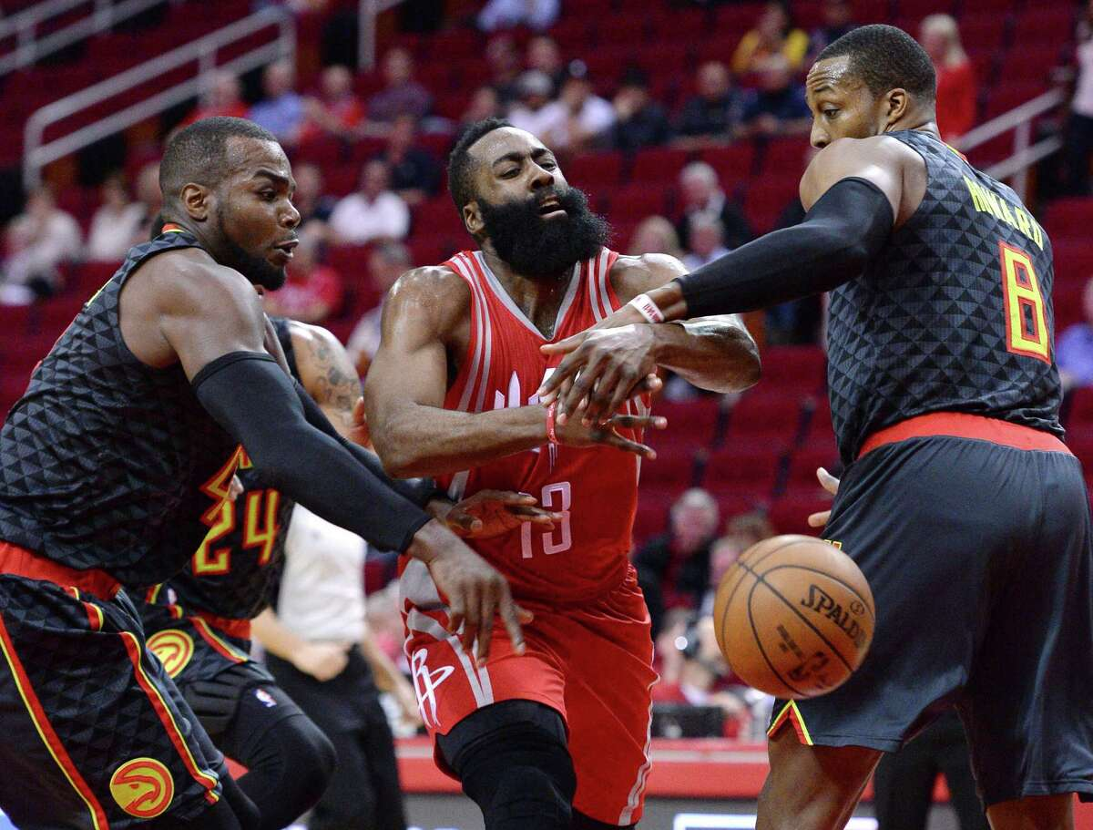 Houston Rockets guard James Harden (13) loses the ball as he drives between Atlanta Hawks forward Paul Millsap, left, and Dwight Howard (8) during the first half of an NBA basketball game Thursday, Feb. 2, 2017, in Houston. (AP Photo/George Bridges)