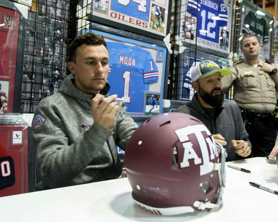 Johnny Manziel prepares to sign a Texas A&M helmet during a paid autograph event at a store in a Katy mall Thursday night.  Photo: Juan DeLeon, FRE / Houston Chronicle