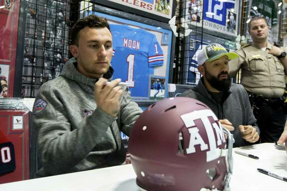 Johnny Manziel prepares to sign a Texas A&M helmet during a paid autograph event at a store in a Katy mall Thursday night.