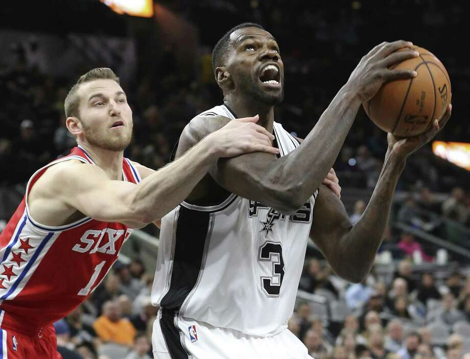 Dwayne Dedman gets held down by Nik Stauskas but makes the layup anyway as the Spurs host the Sixers at the AT&T Center on February 2, 2017. Photo: Tom Reel, Staff / San Antonio Express-News / 2017 SAN ANTONIO EXPRESS-NEWS