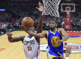 Golden State Warriors guard Ian Clark, right, shoots as Los Angeles Clippers forward Brandon Bass defends during the first half of an NBA basketball game, Thursday, Feb. 2, 2017, in Los Angeles. (AP Photo/Mark J. Terrill)