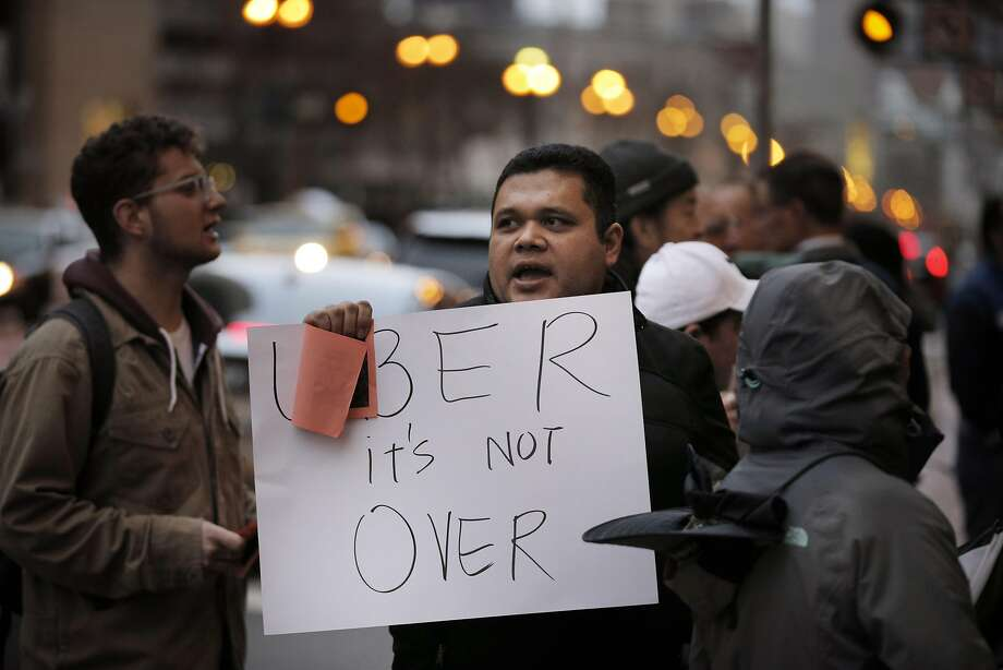 Ramses Teon-Nichols holds a sign as protestors from local nonprofits, such as the East Bay Alliance for a Sustainable Economy, protested outside Uber's headquarters in San Francisco, Calif., on Thursday, February 2, 2017. The various groups wanted to remind Uber CEO Travis Kalanick that they would be vigilant of his connections with President Donald Trump after he quit Trump's  economic advisory council. Photo: Carlos Avila Gonzalez, The Chronicle