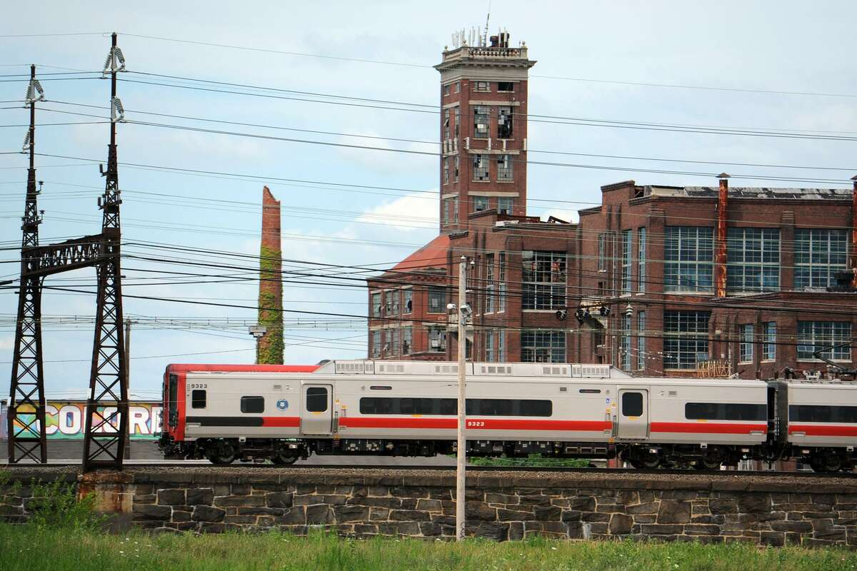 A Metro-North train travels past the former Remington Arms factory, and Shot Tower, in Bridgeport, Conn. July 24, 2014, seen from the vacant Father Panik Village property. A new commuter rail station is planned near this location, tentatively called Barnum Station.