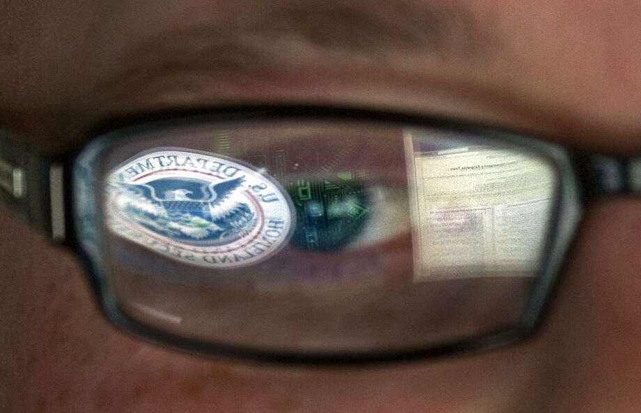 FILE - In this Sept. 30, 2011, file photo, a reflection of the Department of Homeland Security logo is seen reflected in the glasses of a cyber security analyst in the watch and warning center at the Department of Homeland Security's secretive cyber defense facility at Idaho National Laboratory in Idaho Falls, Idaho. Through history, the United States has relied on its borders and superior military might to protect against and deter foreign aggressors. But a lack of boundaries and any rulebook in cyberspace has increased the threat and leveled the playing field today. (AP Photo/Mark J. Terrill, File) Photo: Mark J. Terrill, STF / Associated Press / AP2011
