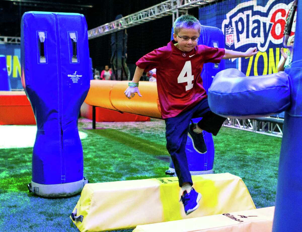 Joshua Green runs through a blocking dummy obstacle course during Super Bowl LI activities at the NFL Experience in the George R. Brown Convention Center on Saturday, Jan. 28, 2017, in Houston. ( Brett Coomer / Houston Chronicle )