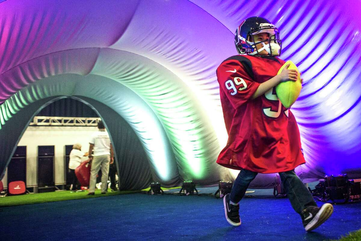 Eric Jew runs through a tunnel wearing a J.J. Watt, of the Houston Texans, jersey during Super Bowl LI activities at the NFL Experience in the George R. Brown Convention Center on Saturday, Jan. 28, 2017, in Houston. ( Brett Coomer / Houston Chronicle )