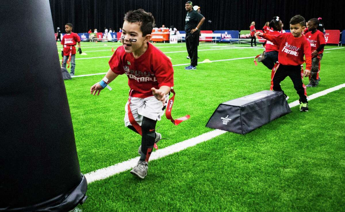 Jake Soule prepares to hit a tackling dummy during football skill drills at the NFL Experience in the George R. Brown Convention Center.