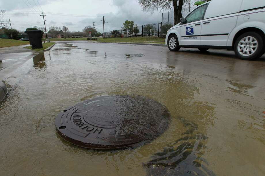 Flood water comes up from a manhole cover near Braesmont and Braeswood on Jan. 18. Fixing Houston's flood-prone areas could receive a boost from increases in infrastructure spending nationally. Photo: Steve Gonzales, Staff / © 2017 Houston Chronicle