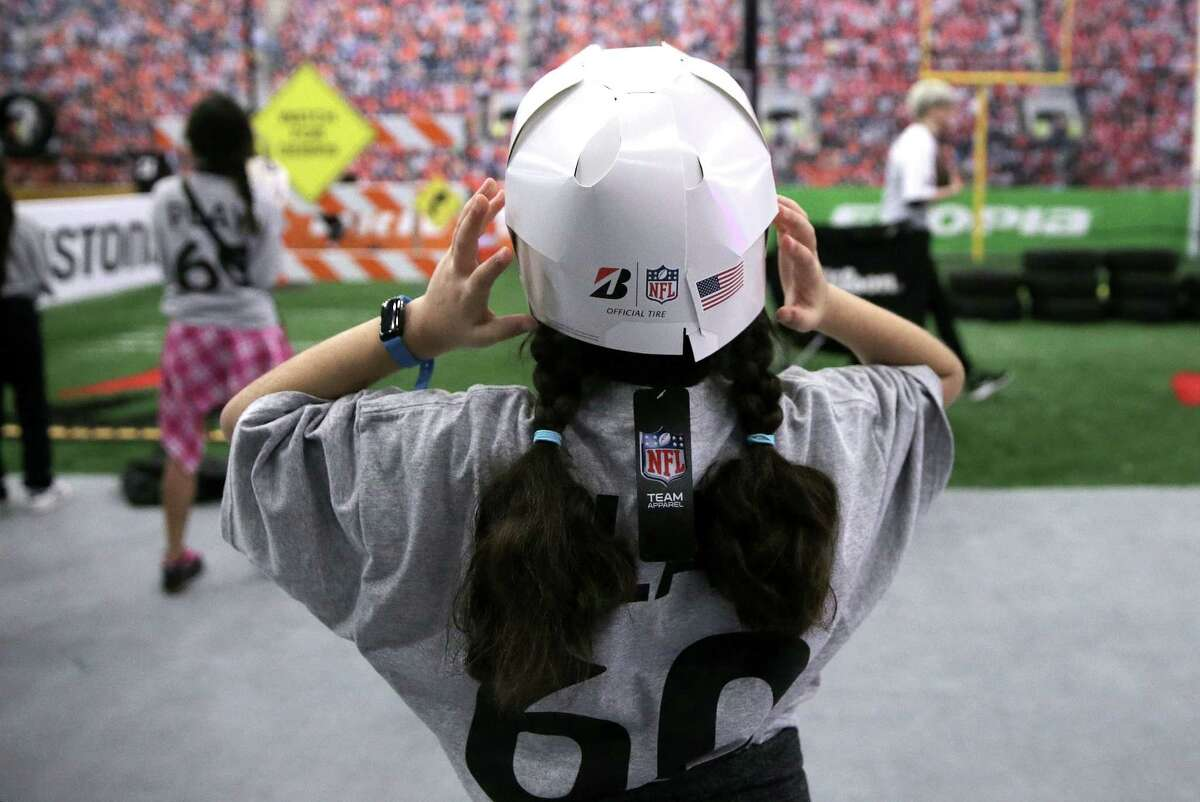 Melissa Hormoz, 10, puts on a paper football helmet with her classmates at Cooper Elementary as they check out the NFL Experience as part of the NFL Play 60 Kids' Day on Wednesday, Feb. 1, 2017, in Houston. ( Elizabeth Conley / Houston Chronicle )