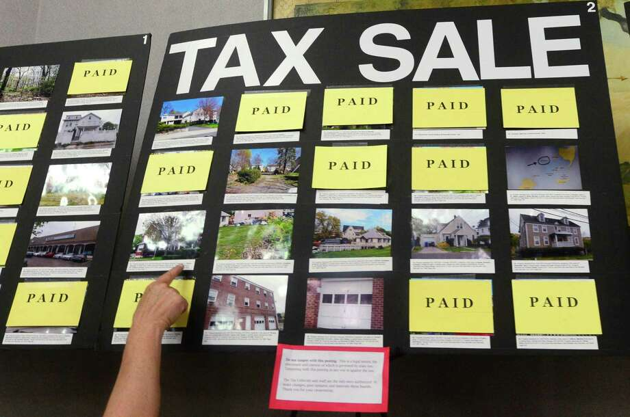 A woman looks at the Tax Sale postings in the Norwalk City Hall atrium in Norwalk, Conn. Tuesday, July 5, 2016. The The Norwalk Tax Collector's Office has collected $3.2 million in advance of the tax sale that will put properties that remain delinquent on the auction block. The tax sale is scheduled for Monday, July 18, 2016, in the Norwalk Concert Hall. Bidder registration begins at 3 pm; the rules of the sale are read at 4 pm, and the sale itself will commence at 5 pm. Photo: Erik Trautmann / Hearst Connecticut Media / Norwalk Hour