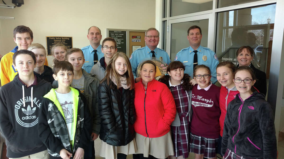 As part of Catholic Schools Week, students at St. Mary's drew pictures, wrote thank you notes and delivered cookies and treats to first responders. Students are pictured here with members of the Edwardsville Police Department.