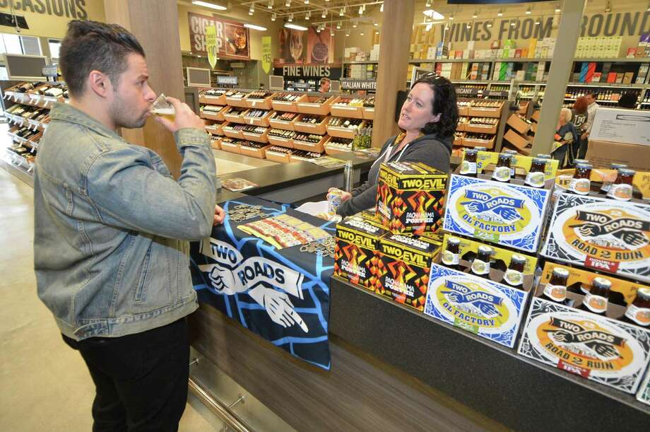Norwalk resident Andrew Dominick samples a Two Roads Brewing beer at a booth staffed by the brewery's Caitlin Guelakis, during the October 2016 grand opening of the new LQR MKT on Connecticut Avenue in Norwalk. New arrivals like LQR and the corporate offices of Crius Energy and Omega Engineering helped push Norwalk to the top of the list for economic momentum in 2016 among southwestern Connecticut cities, according to a Hearst Connecticut Media analysis of jobs, real estate and business expansions and contractions among other criteria. Photo: Alex Von Kleydorff / Hearst Connecticut Media / Connecticut Post